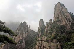 Sanqingshan Mountain in Jiangxi Province, China. Misty mountain scenery with rocky peaks on Mount Sanqing. Sanqingshan is a sacred Taoist mountain famous for its rocky outcrops and lush forests.