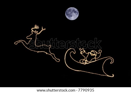 santa and reindeer as silhouetted lights at night, with blue moon