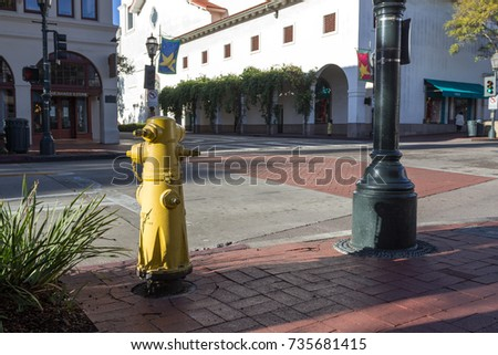 SANTA BARBARA, USA - DECEMBER 24, 2016. Yellow hydrant and part of light pole on the streets of the town #735681415