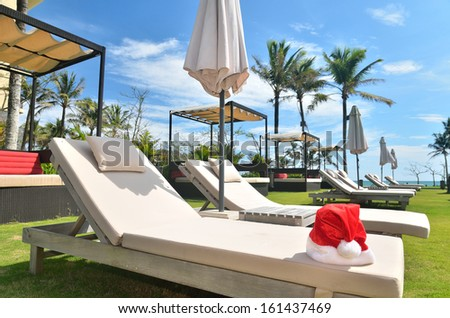 Santa christmas red hat on the sunbed -- Christmas vacation concept