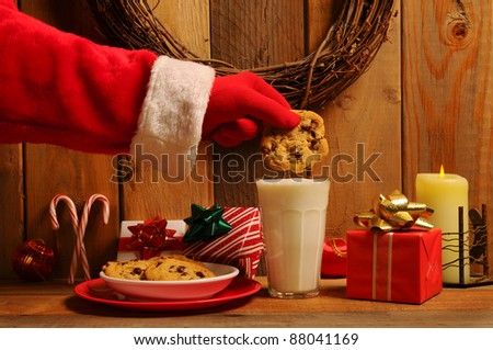 Santa Claus about to dunk a chocolate chip cookie into a glass of milk in a rustic old fashioned setting.