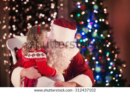 Santa Claus and children opening presents at fireplace. Kids and father in Santa costume and beard open Christmas gifts. Little girl helping with present sack. Family under Xmas tree at fire place.