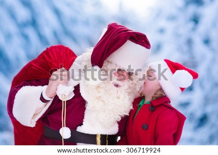 Santa Claus and children opening presents in snowy forest. Kids and father in Santa costume and beard open Christmas gifts. Little girl helping with present sack. Xmas, snow and winter fun for family.