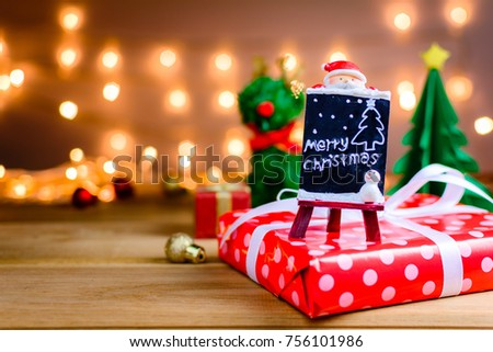 santa claus and gifts and toys on wooden boards and bokeh warm light background with Christmas holidays and happy smile kids.selective focus #756101986