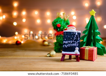 santa claus and gifts and toys on wooden boards and bokeh warm light background with Christmas holidays and happy smile kids.selective focus #758693485