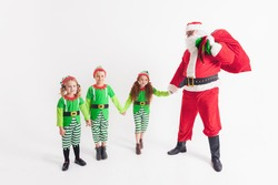 Santa Claus and Kids dressed in Elven costumes. North Pole.