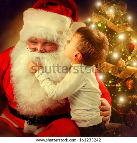 Stock Photo Santa Claus and Little Boy. Christmas Scene. Boy Telling Wish in Santa Claus's Ear in front of Christmas Tree