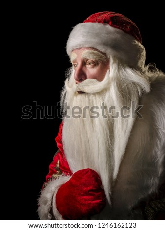 Santa Claus and Santa Claus on a black background. Santa Claus and Santa Claus majestic, looking amazed at the side, in profile against a black background. #1246162123
