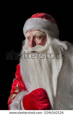 Santa Claus and Santa Claus on a black background. Santa Claus and Santa Claus majestic, looking amazed at the side, in profile against a black background. #1246162126