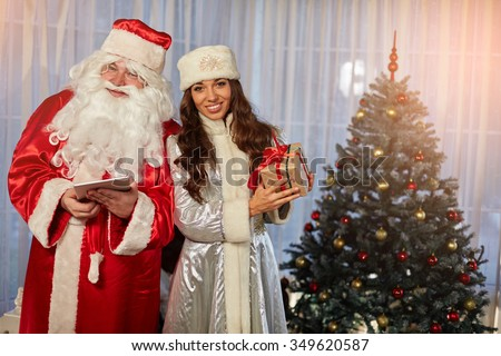 Santa Claus and Snow Maiden give gifts for Christmas