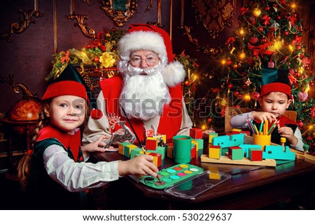 Stock Photo Santa Claus and the elves make gifts for children at Christmas. Workshop of Santa Claus. Christmas concept.