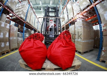 Santa Claus as a forklift operator at work in warehouse. 2 large red sack at the front of forklift.fish-eye lens