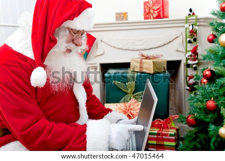 Santa Claus at home with a laptop pointing at the screen