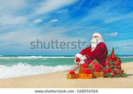 Santa Claus at sea beach with many gifts and decorated christmas tree - happy new year concept