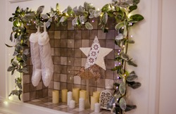 Santa Claus boots and a white Christmas star hang near a fireplace with ceramic tiles. Christmas star hanging from a light photo.