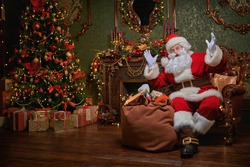 Santa Claus brought gifts for Christmas. He sits in an armchair in a beautiful Christmas interior. Christmas and New Year concept.