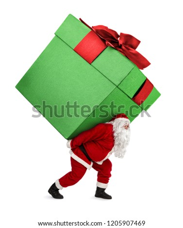 Santa Claus carrying huge christmas gift isolated on white background - Shutterstock ID 1205907469