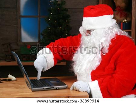 Santa Claus checks his e-mail on his laptop computer