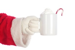 Santa Claus. Christmas Santa Arm. Isolated on white. Room for text. Santa Claus holds a cup of Hot Coco with a Candy Cane and Whip Cream. Santa Loves Hot Coco and Cookies on Christmas.