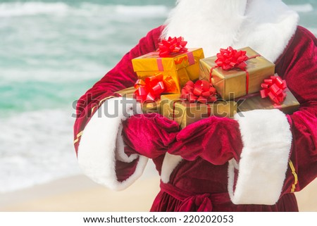 Santa Claus close up with many golden gifts on sea beach - christmas or happy new year concept