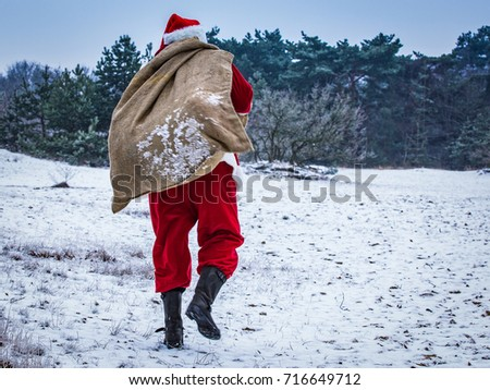 Santa Claus coming to the winter forest with a bag of gifts, snow landscape, #716649712