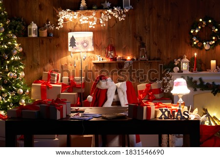 Santa Claus costume and hat hanging on chair at table with Merry Christmas decor gifts presents on holiday eve in cozy Santa home workshop interior late in night with light on xmas tree and fireplace.