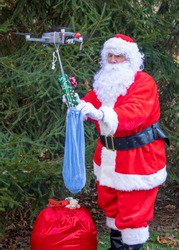 Santa Claus delivering Christmas gifts using drone.