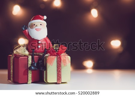 Santa Claus dolls and Christmas decorations box on abstract light background with copy space