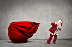 Santa Claus dragging his very large full of presents