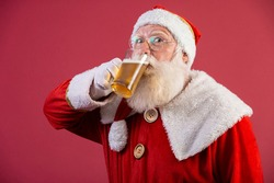 Santa Claus drinking a glass of beer. Rest time. Alcoholic drink at the holidays. Drink with moderation. Craft beer. Merry Christmas.