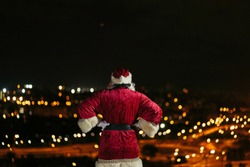 santa claus from the back with hands on the hip looking the city at night