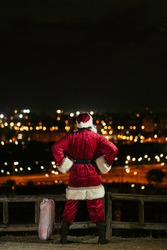 santa claus from the back with hands on the hip looking the city at night with presents bag