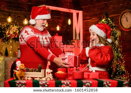 Santa Claus generous. Child enjoy christmas with bearded grandfather Santa claus. Happiness and joy. Rewarding kindness. Santa bring gifts little girl. Cheerful celebration. Festive tradition.