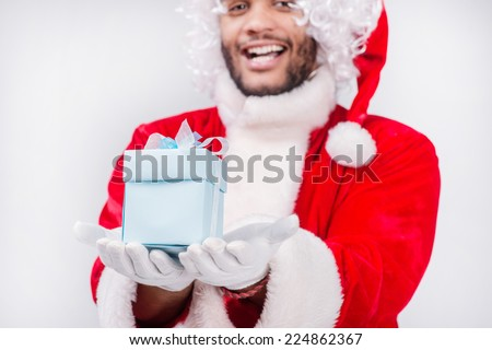 Santa Claus giving a gift at Christmas. Laughing and smiling African male Santa Claus giving a gift on Christmas Eve while standing on an isolated white background