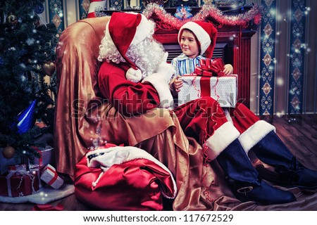Santa Claus giving a present to a little cute boy near the fireplace and Christmas tree at home.