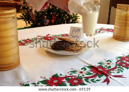 santa claus grabs a glass of mild kindly left for him with a plate of cookies as a snack and thank you on xmas eve