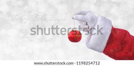 Santa Claus hand holding a red tree ornament over a silver bokeh background with snow effect. Banner size with copy space and the words Merry Christmas.