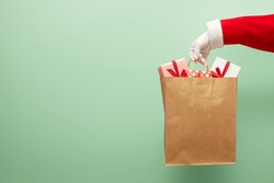 Santa Claus hand holding brown shopping bag paper with gift boxes on green isolated background.