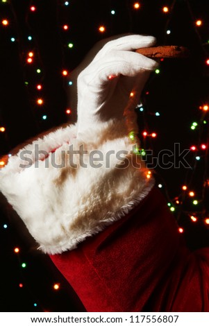 Santa Claus hand holding chocolate cookie on bright background
