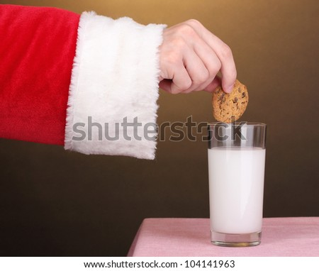 Santa Claus hand holding chocolate cookie on brown background - stock photo
