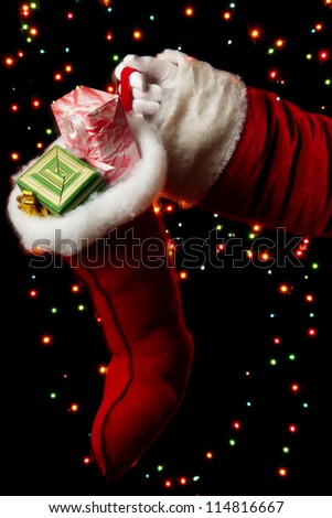 Santa Claus hand holding gifts on bright background - stock photo