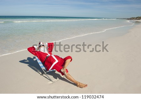 Santa Claus happy relaxed sitting with hands up at beach, having fun and joy off duty at tropical holiday vacation, isolated with ocean and blue sky as background and copy space.