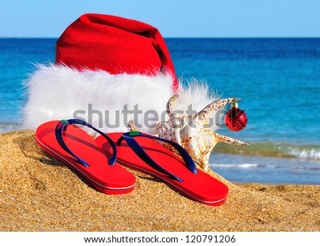 Santa Claus hat and slippers on the seashore against blue sky