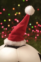 Santa Claus hat on football with Christmas lights