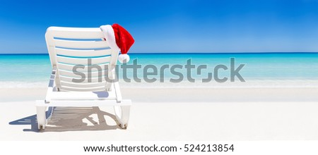 Santa Claus Hat on sunbed near tropical calm beach with turquoise caribbean sea water and white sand. Christmas vacation celebration