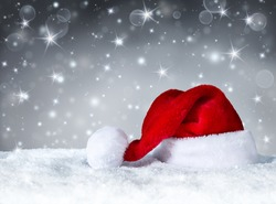 Santa Claus hat with snow and silver snowfall background
