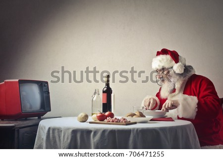Santa Claus having dinner in front of the tv