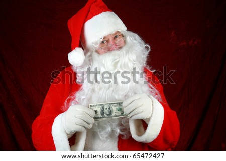 Santa Claus hold money in preparation to give to you for christmas or the concept of the high cost of christmas against a red velvet background