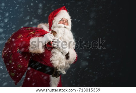 Santa Claus holding a bag with presents and ringing a bell on a dark background with snow  #713015359