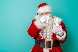 Santa Claus holding a box of paper tissues, blowing nose, sick, having flu and fever isolated on mint colored background